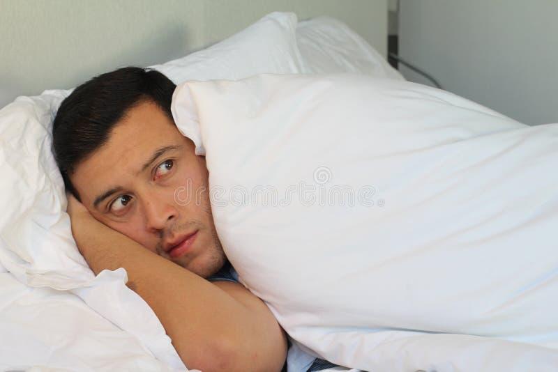 Esconder masculino delusório sob as coberturas foto de stock