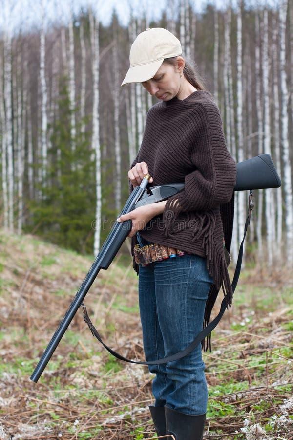 Escopeta del cargamento del cazador de la mujer en la caza fotografía de archivo