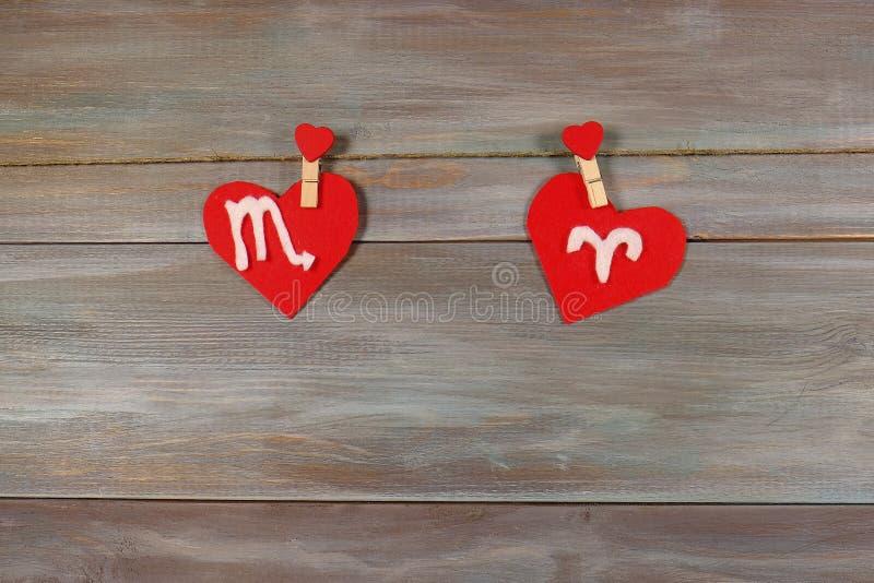 Escorpião e Áries sinais do zodíaco e do coração Backgro de madeira fotos de stock royalty free