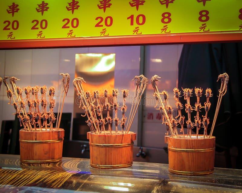 Escorpião e cavalos marinhos em uma vara - alimento chinês típico imagens de stock