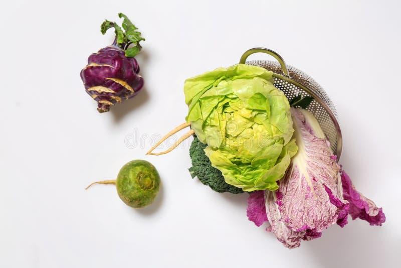 Escorredor virado com os legumes frescos no fundo branco imagem de stock