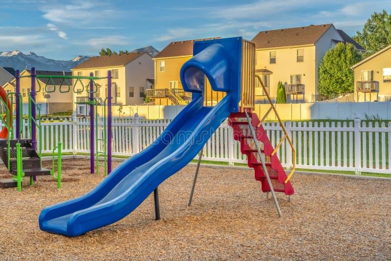 Escorrega azul com escadas vermelhas no playground contra casas montanha e céu azul imagens de stock royalty free