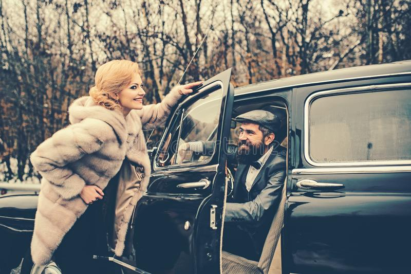 Escort of girl by security. Bearded man and sexy woman in fur coat. Couple in love on romantic date. Retro collection royalty free stock photos