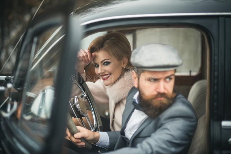 Escort of girl by security. escort concept with bearded driver and luxury girl in retro car. stock photography