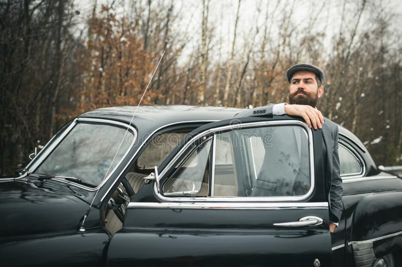 Escort man or security guard. Bearded man in car. Call boy in vintage auto. Retro collection car and auto repair by royalty free stock photo