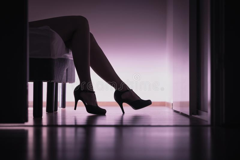 Escort, prostitute or sugar babe lying on bed with long legs and sexy high heels. Prostitution, sex work or sugar dating. royalty free stock image