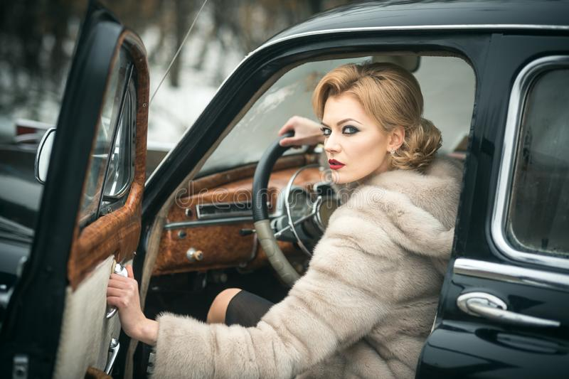 Escort and security guard for luxury woman. sexy woman in fur coat. Call girl in vintage car. Retro collection car and stock image