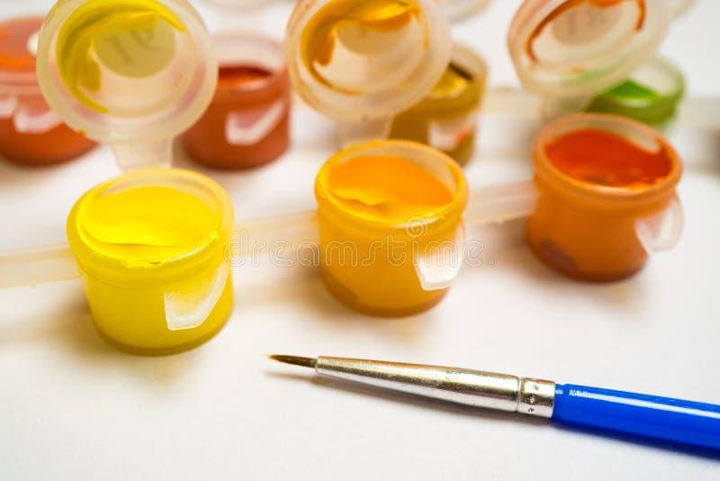 Escova azul para tirar e recipientes com pintura colorida em um fundo branco, arte do ` s das crianças imagem de stock