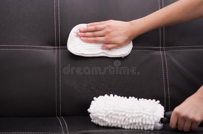 Escova branca da tela da máquina de limpeza de vapor que está sendo usada no sofá de couro preto, sofá da fricção da mão com pano imagem de stock royalty free