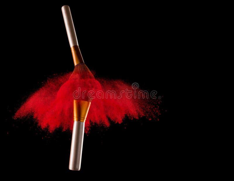 Escova da composição com explosão vermelha do pó no fundo preto foto de stock