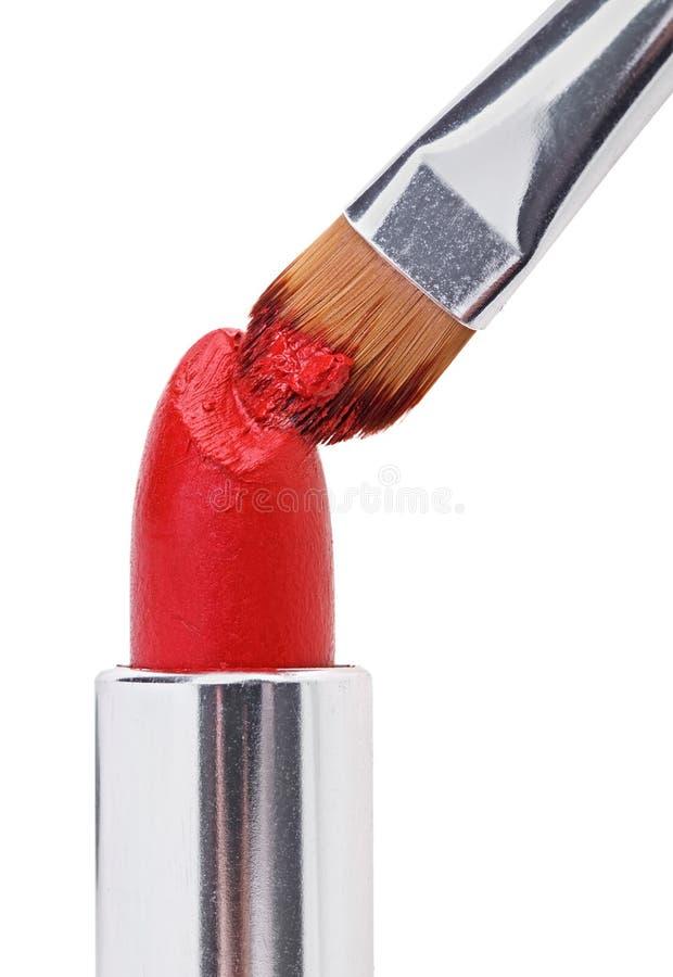 Escova da composição empurrada dentro no batom vermelho fotografia de stock