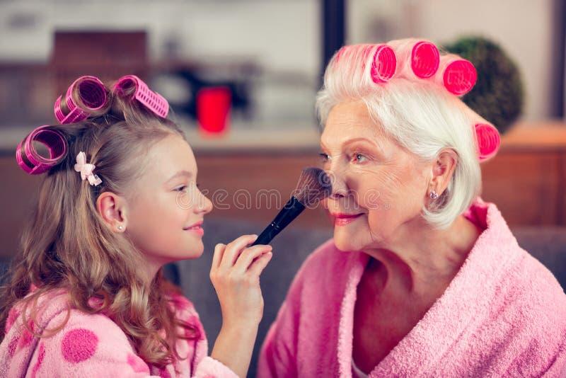 Escova da terra arrendada da menina e facepowder da colocação na cara da avó foto de stock royalty free