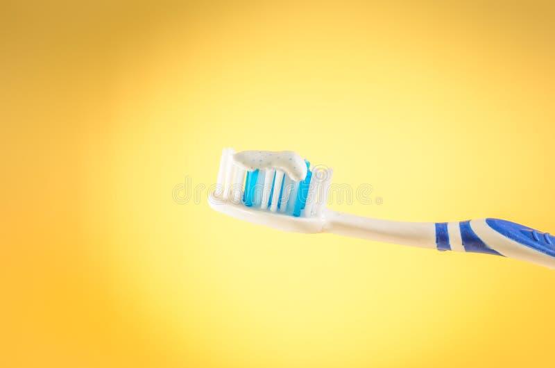 Escova de dentes com dent?frico em um fundo amarelo, fim acima foto de stock royalty free