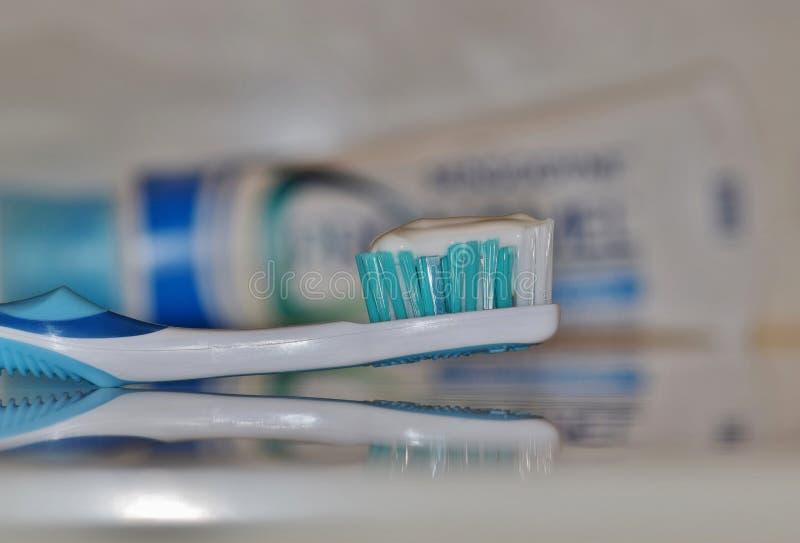 Escova de dentes com o dentífrico branco que senta-se na contador-parte superior imagens de stock royalty free