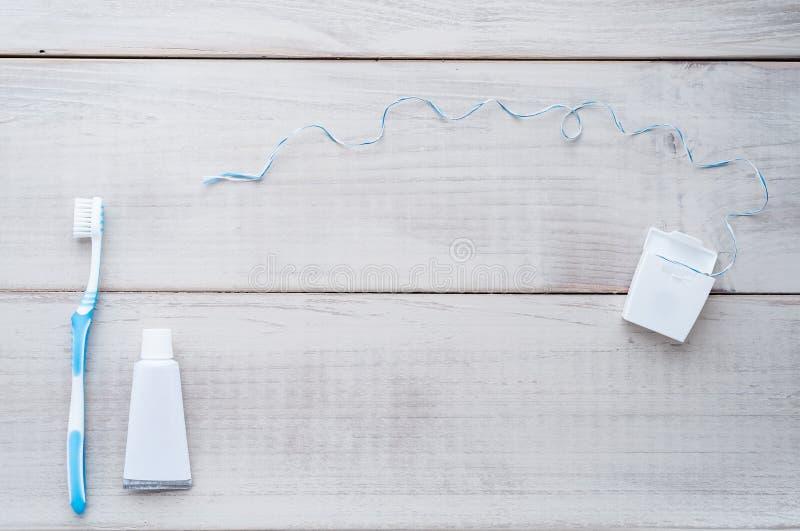 Escova de dentes, dentífrico e fio dental em uma parte traseira resistida da madeira fotografia de stock royalty free