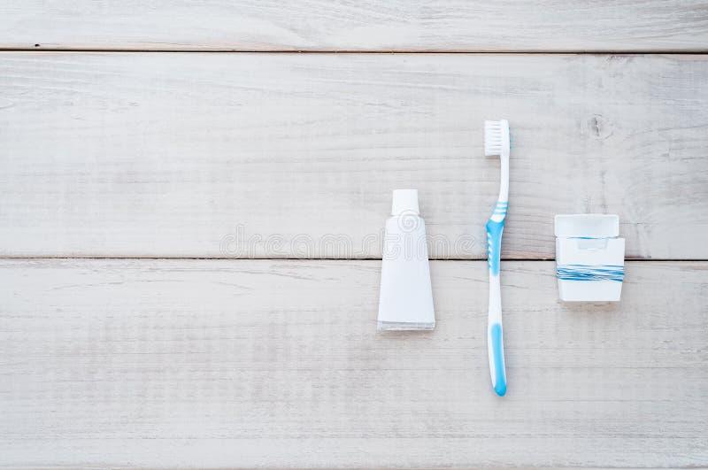 Escova de dentes, dentífrico e fio dental em uma parte traseira resistida da madeira foto de stock