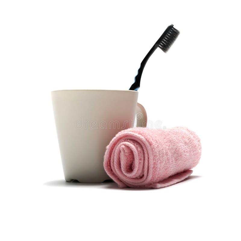 Escova de dentes e toalha com caneca fotografia de stock royalty free