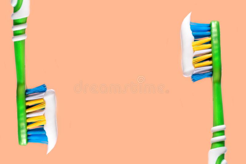 Escova de dentes espremida em um fundo alaranjado do dent?frico da escova de dentes imagem de stock