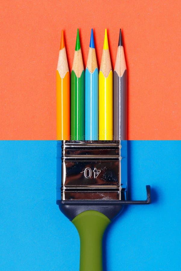 A escova de pintura combinou com os lápis coloridos em um fundo vermelho-azul de duas cores imagens de stock