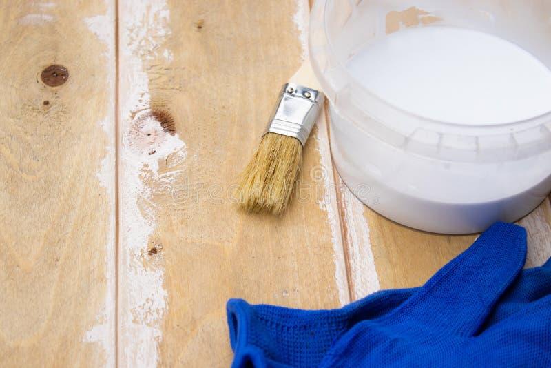 Escova de pintura e uma lata com pintura branca nas placas, preparando uma superfície de madeira para o conceito de pintura foto de stock royalty free