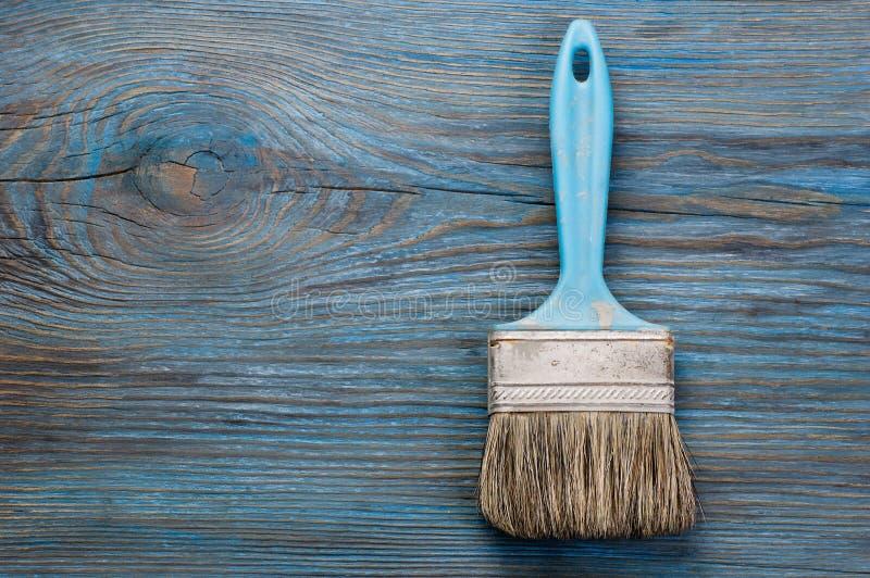 Escova de pintura usada na placa de madeira azul com lugar para o texto fotos de stock