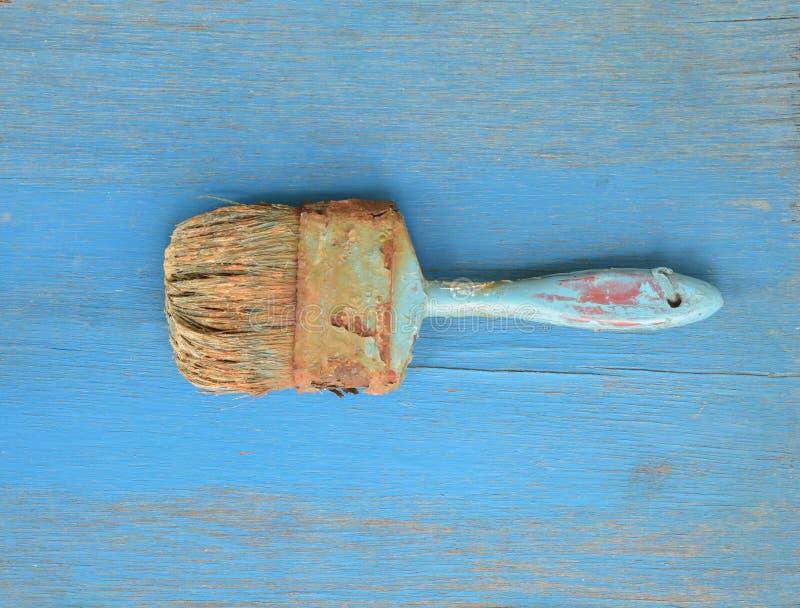 Escova de pintura velha na madeira azul fotos de stock royalty free