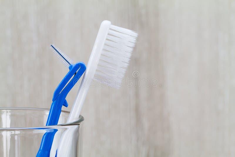 Escova e escova de dentes Interdental no vidro limpo no fundo de madeira borrado no banheiro fotografia de stock royalty free