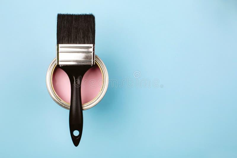 Escova na lata aberta da pintura cor-de-rosa no fundo pastel azul foto de stock