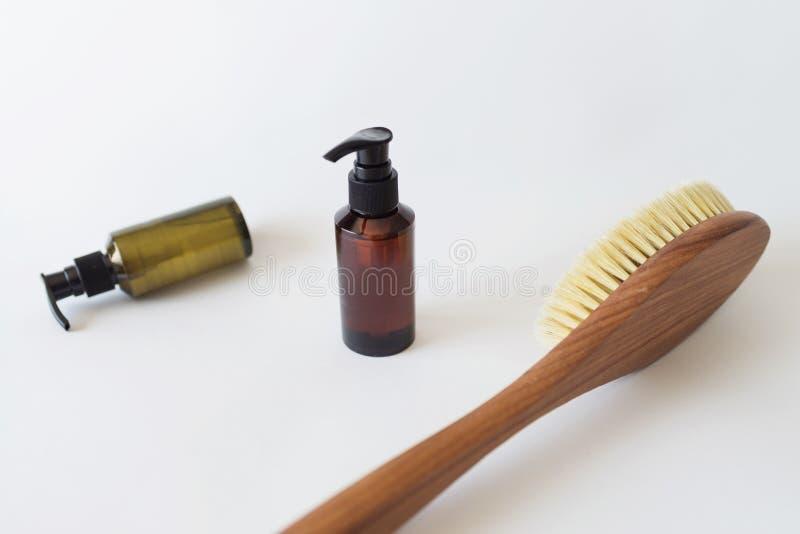 Escova orgânica dos termas para a massagem seca e uma garrafa do óleo do corpo Escova do cacto massagem das Anti-celulites Concei fotografia de stock
