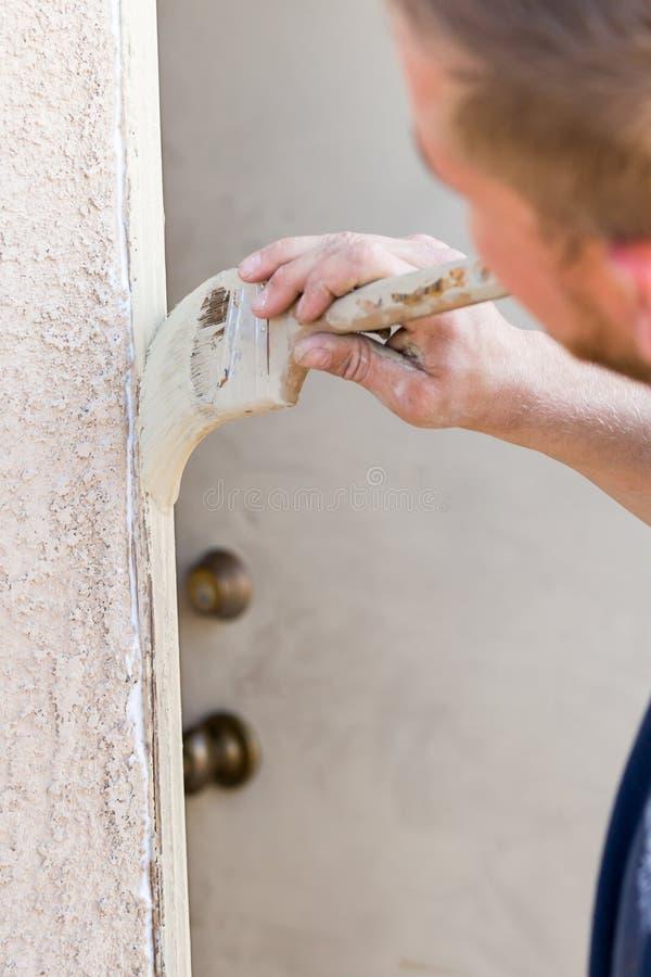Escova profissional de Cutting In With do pintor para pintar a porta F da casa fotografia de stock