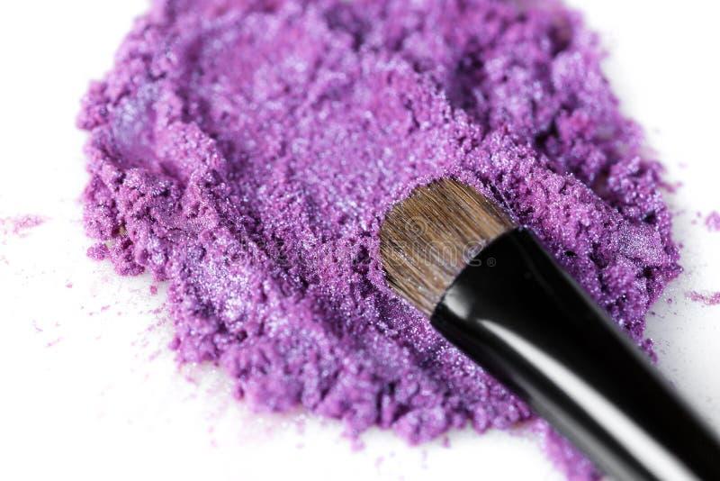 Escova roxa esmagada da sombra para os olhos e da composição isolada no fundo branco imagem de stock royalty free