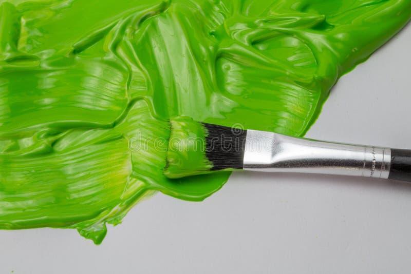 Escova verde da pintura e da arte com cursos lustrosos grossos no pap branco fotos de stock royalty free