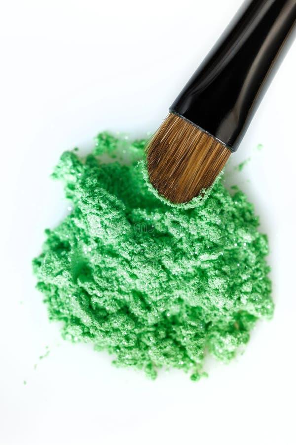 Escova verde quebrada da sombra para os olhos e da composição isolada no fundo branco fotos de stock