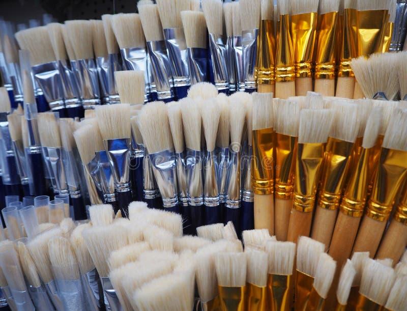 Escovas brancas e azuis para pintar na loja da arte imagem de stock