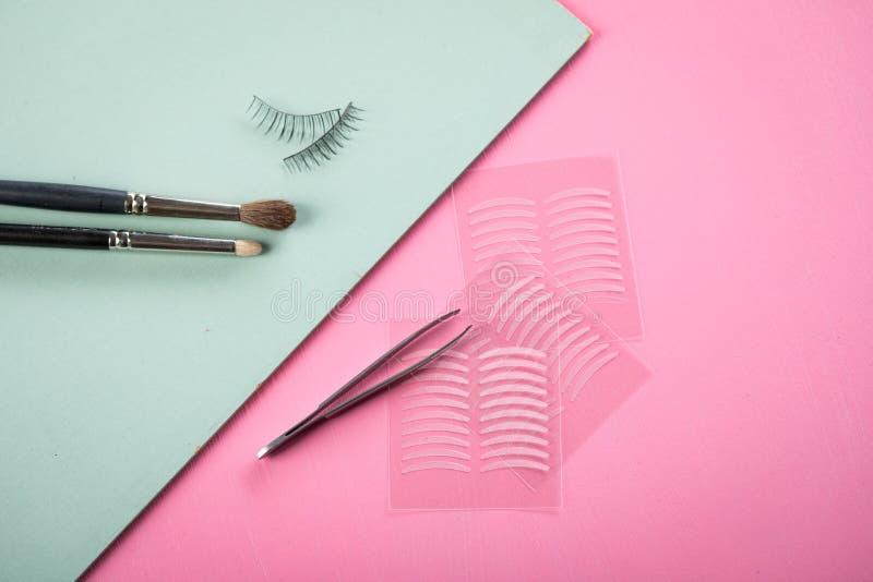 Escovas, chicotes falsificados, pinça e fitas dobro do vinco artificial da pálpebra para a composição do olho no verde do rosa co fotos de stock