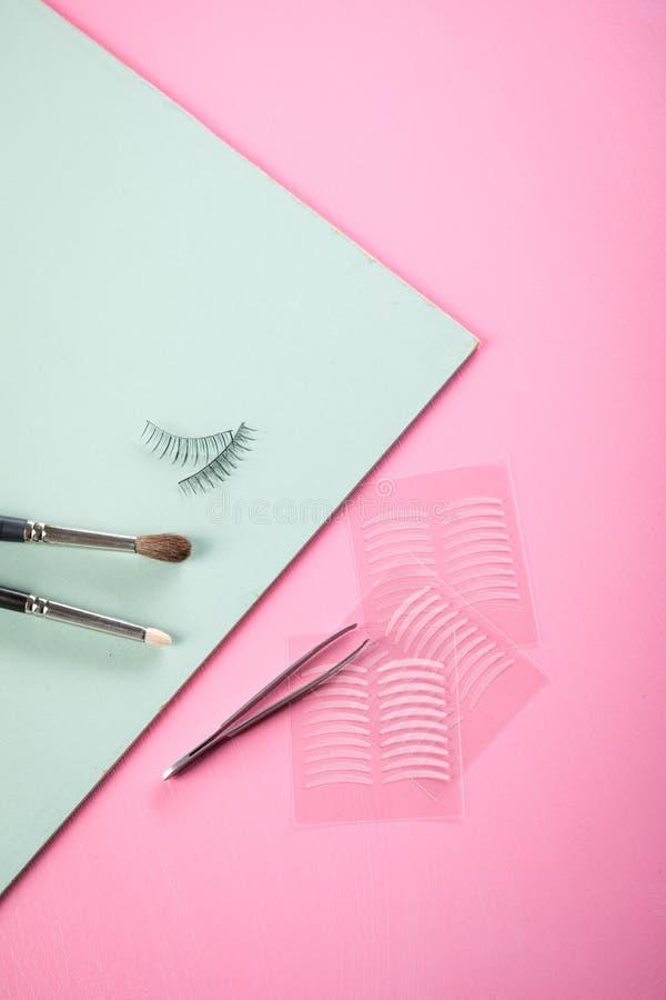 Escovas, chicotes falsificados, pinça e fitas dobro do vinco artificial da pálpebra para a composição do olho no verde do rosa co foto de stock