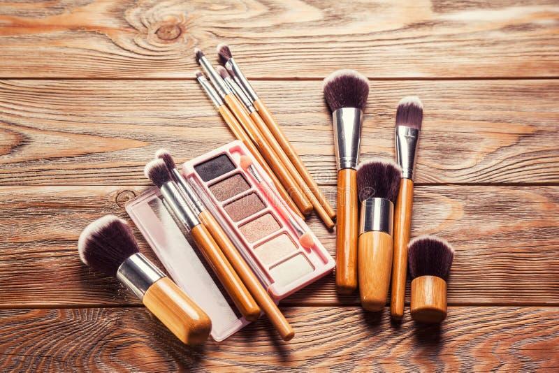 Escovas com os cosméticos dispersados caoticamente fotos de stock royalty free