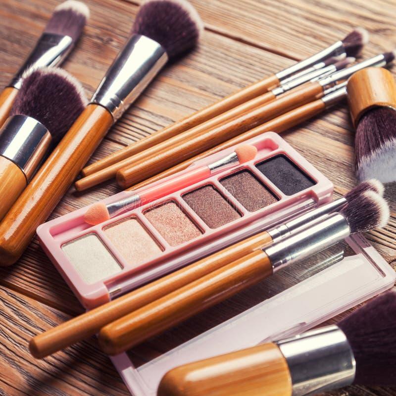 Escovas com os cosméticos dispersados caoticamente imagens de stock royalty free