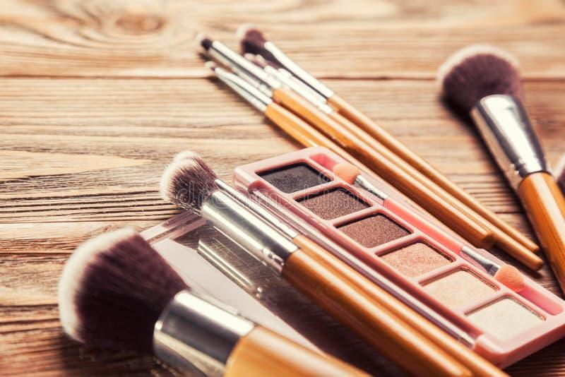 Escovas com os cosméticos dispersados caoticamente fotografia de stock