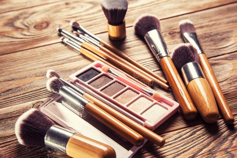Escovas com os cosméticos dispersados caoticamente fotos de stock