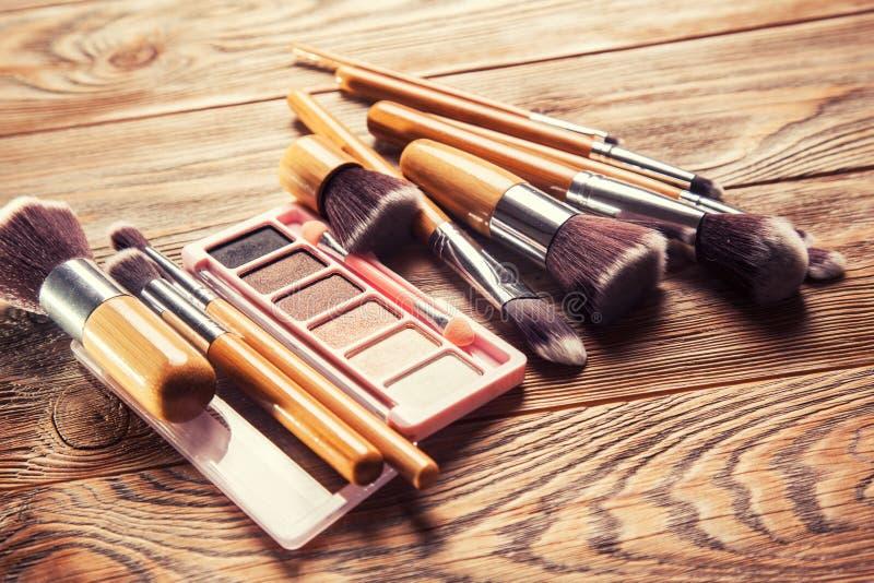 Escovas com os cosméticos dispersados caoticamente imagens de stock