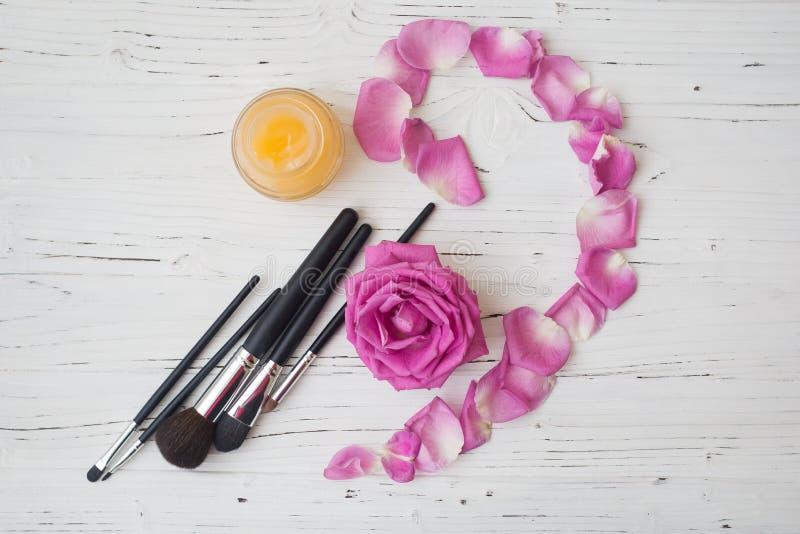 Escovas, creme amarelo e rosa do rosa na tabela de madeira branca imagem de stock royalty free
