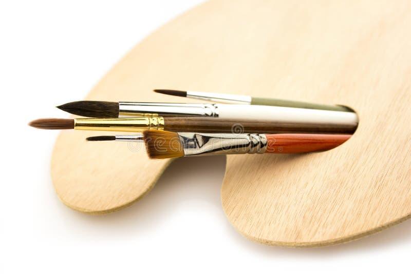 Escovas da arte na paleta de madeira isolada no branco imagem de stock royalty free