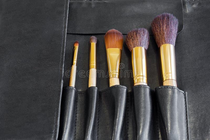 Escovas da composição em uma tampa preta imagens de stock