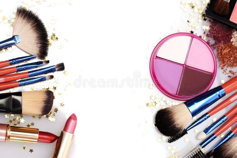 Escovas da composição no suporte e nos cosméticos fotografia de stock