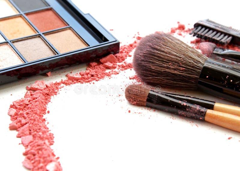 escovas da composição no suporte e nos cosméticos isolados no branco foto de stock