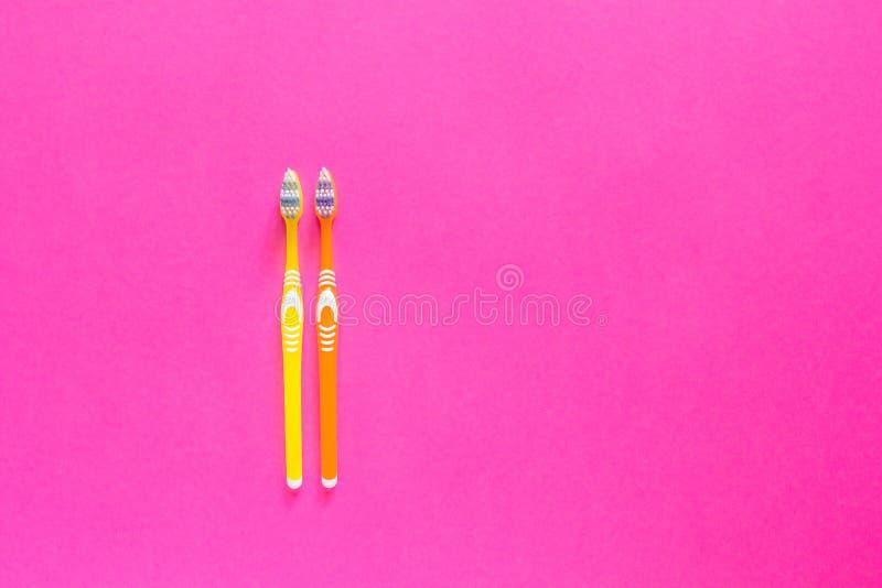Escovas de dentes amarelas e alaranjadas em um fundo cor-de-rosa brilhante cópia foto de stock royalty free