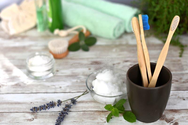Escovas de dentes de bambu de madeira no vidro marrom escuro fotografia de stock