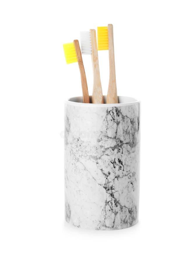 Escovas de dentes de bambu no suporte no fundo branco foto de stock