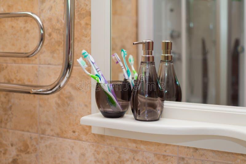 Escovas de dentes coloridas em um vidro preto fotografia de stock